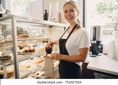 Portrait of white Caucasian beautiful barista woman taking muffin pastry from shop-window. Person at work place, small business concept