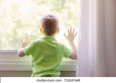 Portrait of white Caucasian child boy at home looking out of window outside. View from back. Kid waiting for someone