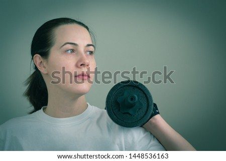 Portrait of a white caucasian woman holding heavy iron dumbbells close-up. Toned image in blue