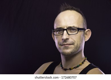 Portrait of a white man direct looking in glasses on dark background