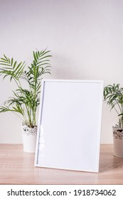 Portrait white picture frame mockup on wooden table. Modern vases with palms. White wall background. Scandinavian interior.