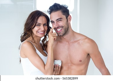 Portrait wife smiling while applying cream on husband face at home