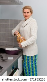 Portrait of wife standing at domestic kitchen