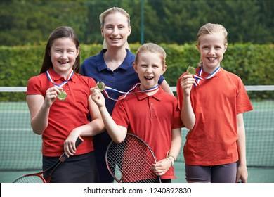 Portrait Of Winning Female School Tennis Team With Medals