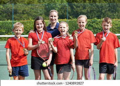 Portrait Of Winning School Tennis Team With Medals
