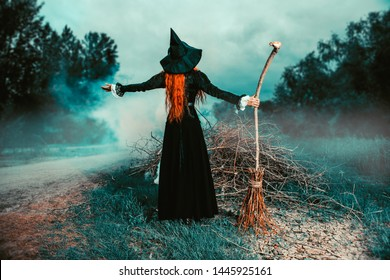 A portrait of a witch with a broodstick near the forest. Magic, dark force, spell.