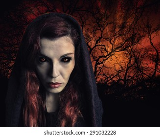 Portrait of a witch with scary eyes and a wood on fire in background.