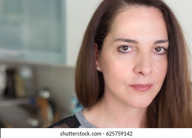 Portrait of a woman 45 years old looking at camera, serious, thinking.