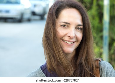 Portrait of a woman 45 years old, looking at camera, smiling, urban background, outdoors.