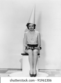 Portrait of woman with April Fool sign wearing dunce cap