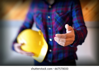 Portrait of  woman  architect with safety  helmet greeting her partner. woman builder showing handshake. Partnership concept.