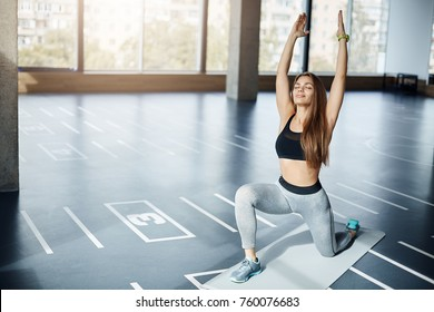 Portrait of woman athlete relaxing and breathing deep in yoga pose in empty morning gym environment. Fitness trainer getting ready for workout before her client arrives.