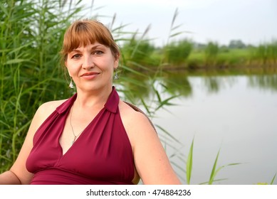 Portrait of the woman of average years against the background of the lake