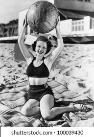 Portrait of woman with ball at beach