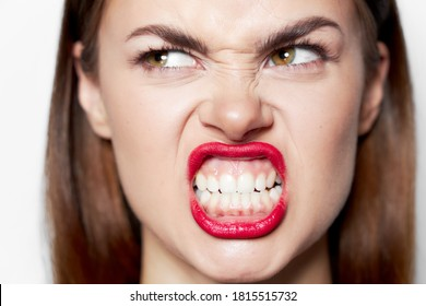 Portrait of a woman bares her teeth and looks aside a grimace