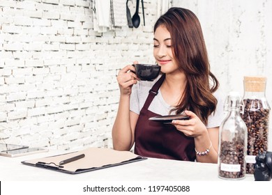 Portrait of woman barista small business owner smiling and holding cup of coffee behind the counter bar in a cafe