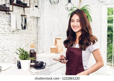 Portrait of woman barista small business owner smiling  behind the counter bar in a cafe