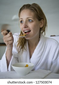 Portrait of a woman in bathrobe eating cereal for breakfast