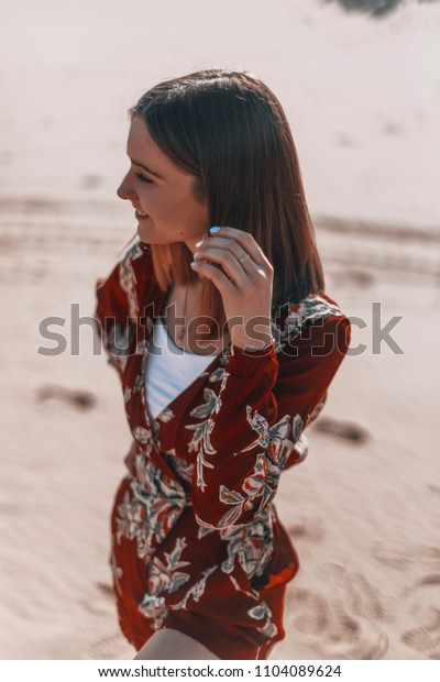 portrait of woman in the beach or desert. beauty tourist in hot climate country. girl is lokking down. female is rest.