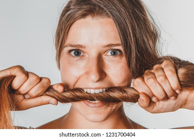 Portrait of woman with beautiful long hair bites his hair.
