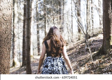 Portrait of woman with beautiful long hair walking in a forest on a sunny day
