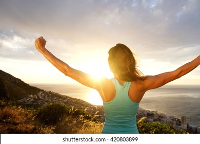 Portrait of woman from behind stretching out her arms in front of sunrise