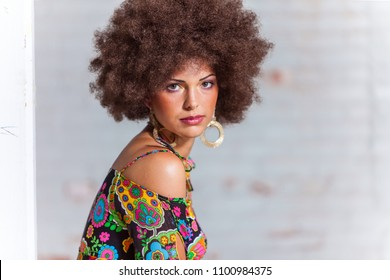 Portrait of woman with big hair wearing 1970s style clothing