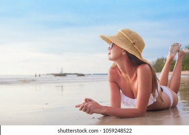 portrait of woman in bikini and straw hat relaxing on tropical beach
