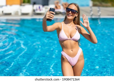 Portrait of a woman in bikini and sunglasses making selfie photo on smartphone wave hello for social media at pool