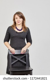 Portrait of woman in black dress propping hands on back of chair in studio.
