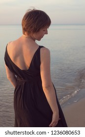 Portrait of a woman in a black dress with a short haircut from the back