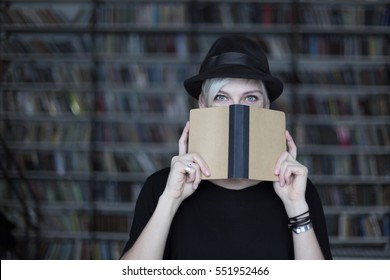 Portrait of woman in black hat with opened book, face half-covered, white hair. Hipster student girl in a library