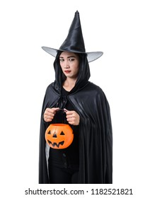Portrait of woman in black Scary witch halloween costume standing with hat and holding a pumpkin isolated on white background with clipping path