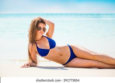 Portrait of woman in black swim posing on tropical beach