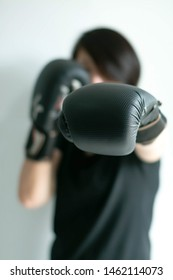A portrait of woman in black T-shirt and black boxing gloves stretching her left fist forward; Left jab; selected focus at tip of the fist.