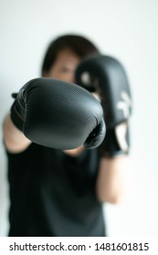 Portrait of woman in black T-shirt and black boxing gloves stretching her right fist forward; right jab; sport and health care; selected focus at tip of the fist. Concept of aim in business.