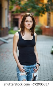 Portrait of a woman in a black T-shirt and jeans standing in the courtyard of an old house.