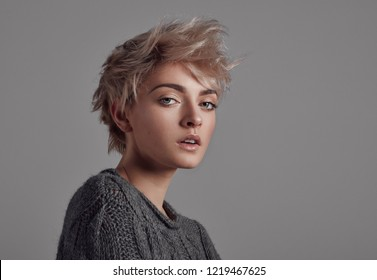 Portrait of woman with blond short hair isolated on gray background