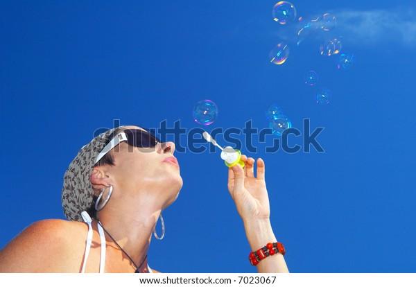 portrait of a woman blowing bubbles on blue sky back
