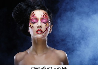 Portrait of woman with bright artistic make-up over smoke  background