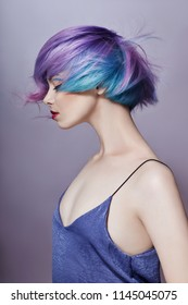 Portrait of a woman with bright colored flying hair, all shades of purple. Hair coloring, beautiful lips and makeup. Hair fluttering in the wind. Sexy girl with short hair