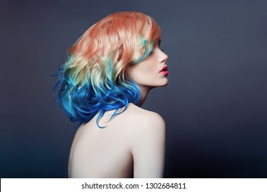 Portrait woman with bright colored flying hair, all shades purple blue. Hair coloring, beautiful lips and makeup. Hair fluttering in wind. Sexy girl with short  hair. Professional creative coloring