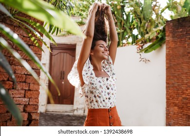 Portrait of woman in bright skirt and blouse with floral print raising her hair. Girl in high spirits poses against background of house with old wooden doors and tropical trees