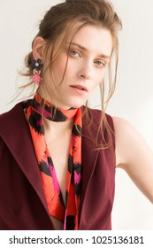 Portrait of a woman with brown hair in a burgundy vest with a colored headscarf and bright  earrings