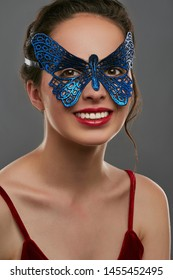 Portrait of woman with brunette hair, wearing wine red crop top. The smiling girl is looking at the camera, wearing blue butterfly-shaped carnival mask with perforation. Vintage carnival accessory.