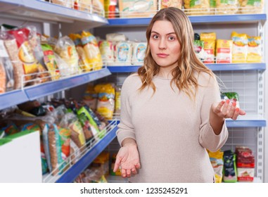 Portrait of woman buyer standing near assortment of grocery food store
