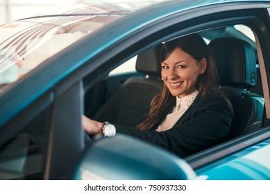 Portrait of woman in car in car salon.