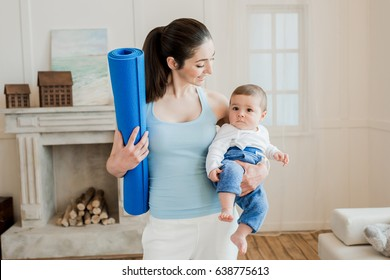 Portrait of woman carrying her happy baby child on arm and holding yoga mat at home