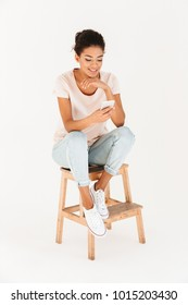Portrait of woman in casual sitting on chair and holding mobile phone in hands isolated over white background
