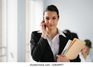 Portrait of a woman with cell phone and documents